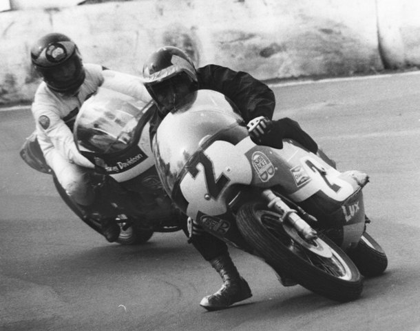 Mert Lawwill betrays his flat track roots as he corners his Harley-Davidson foot down in the popular Anglo-American Transatlantic Match Races at Mallory Park in 1973. Behind Lawwill is Gary Fisher racing with a helmet borrowed from Barry Sheene. (Jim Greening photo)