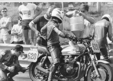 Lynn Miller checks competitor's tire during a pit stop.
